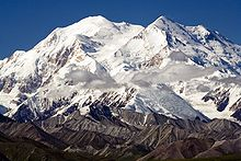 Mount McKinley, covered in snow at the top, and green and brown near the bottom. Some wispy clouds are in the middle.