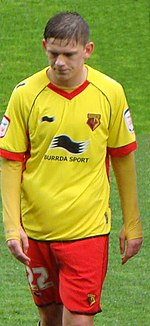 A young man wearing a yellow shirt and red shorts, standing on a grass field