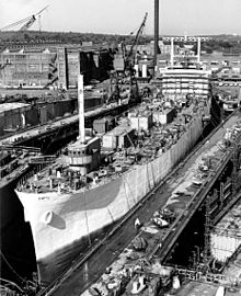 A large ship sits in drydock at the yard, with cranes in the background