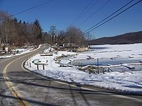 A road winding by the shore of a frozen lake and some docks in wintertime. There are telephone lines over the road, light snow on the ground, and a wooded hill on the far side of the lake at the right of the image