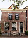 foto van Pand met lijstgevel met voordeur met bovenlicht, forse lijst en dakkapel met schulprand en zijvleugels