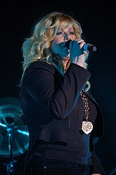 A woman with long blonde hair wearing dark clothing and singing into a microphone