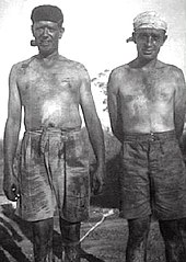 Two men stripped to waist and covered in coal dust, one smoking a pipe