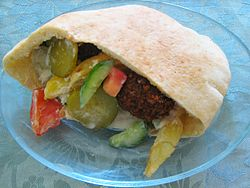 A pita filled with vegetables and fritters on a plate