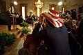 President George W. Bush addresses the audience in the East Room as actor Rob Schneider, decked out in a patriotic cowboy hat, takes a photograph.jpg
