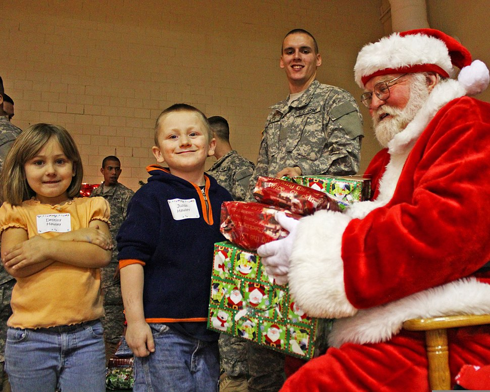 Pvt. Evan Allen Dancer, center, smiles as Santa Claus, right, hands gifts to Destiny Hawley and her brother Justin Hawley of Scipio, Ind., during the 3rd Annual Operation Christmas Blessing event at Muscatatuck 111212-A-QU728-005