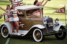 """Seis mujeres, vestido con un uniforme de una falda blanca y un blanco y oro recortar la parte superior con la palabra """"tecnología"""" en el frente, el paseo a la cancha de fútbol en los estribos y el asiento trasero de un coche antiguo blanco y pintado a oro ."""