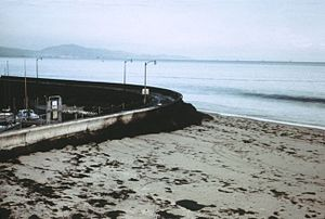1969 Santa Barbara oil spill - Oil piled up at the seawall near the Santa Barbara Harbor. Note the blackness of the incoming wave; the water has a thick layer of oil on top.