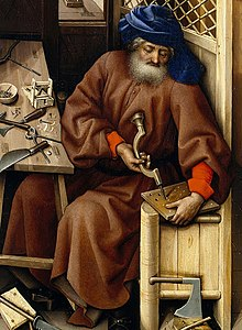 A narrow section from a wing of a large painted altarpiece. Joseph is shown as an old man in a thick brown robe and blue turban. He is seated on a tall high-backed seat with a work bench in front of him. He is drilling a piece of wood. Other tools shown on the bench and floor are a hammer and chisel, an axe, an adze, a rasp, a knife, a gimlet and a plane.