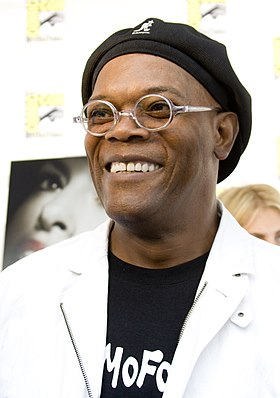 "An African-American man is at the centre of the image looking to the left and smiling. He is wearing a hat, glasses, a white jacket and a black t-shirt that says ""MoFo""."