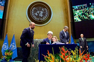 Signing by John Kerry in United Nations General Assembly Hall for the United States Secretary Kerry Holds Granddaughter Dobbs-Higginson on Lap While Signing COP21 Climate Change Agreement at UN General Assembly Hall in New York (26512345421).jpg