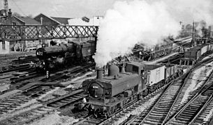 Two steam engines are passing through a station. On the left is a large passenger express locomotive, and on the right, slightly ahead, is a pannier tank locomotive pulling a goods train of open wagons and a flat bogey. It looks as though the locomotives are racing, but as the plumes of steam from the locomotives are at different angles, the fast express will probably quickly catch up with the pannier and pass it.