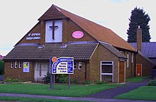 Brick-faced church with a 45-degree tiled gable roof, with a large front-mounted cross on a white background, on grassy land, c. 2004.