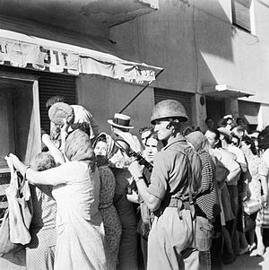 6th Airborne Division in Palestine - A soldier of the British 6th Airborne Division maintains order outside a baker's shop in Tel Aviv.