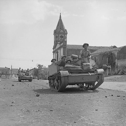 Universal carriers of the 2nd Battalion, Wiltshire Regiment pass through Pedara, Sicily, 9 August 1943.