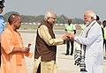 The Prime Minister, Shri Narendra Modi being received by the Governor of Uttar Pradesh, Shri Ram Naik and the Chief Minister of Uttar Pradesh, Yogi Adityanath, on his arrival, at Varanasi, Uttar Pradesh on March 12, 2018.jpg