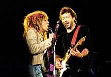 Turer and Clapton, on stage, sharing a microphone stand, singing.