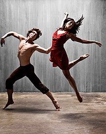 A man and woman, mid-leap