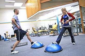 Personal trainer - A personal trainer demonstrating use of a Bosu ball.