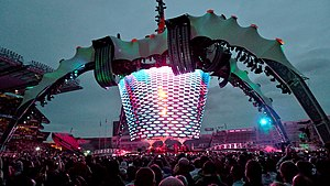 A concert stage; four large legs curve up above the stage and hold a video screen which is extended down to the band. The legs are lit up in green. The video screen has multi-coloured lights flashing on it. The audience surrounds the stage on all sides.
