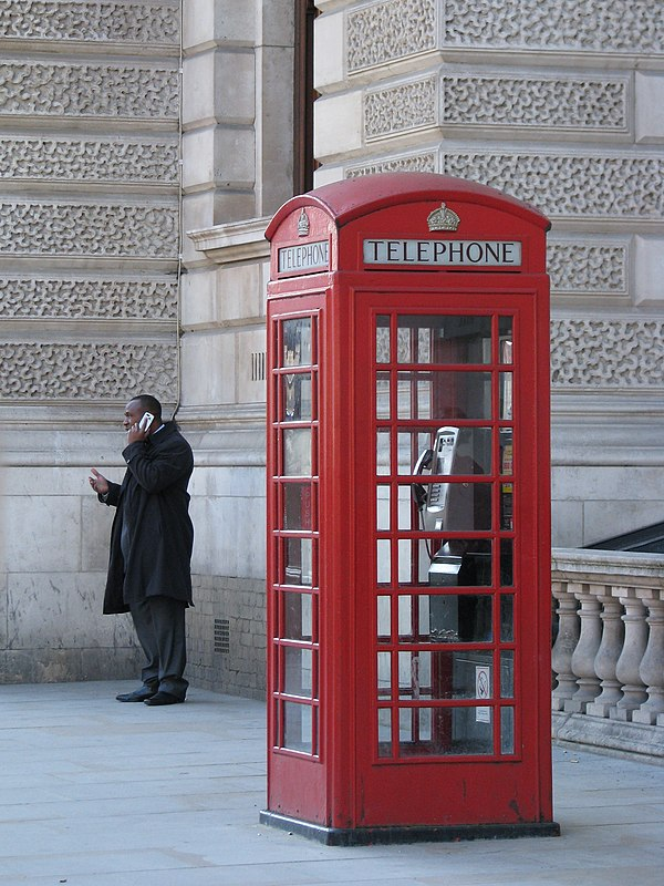 A man talks on his mobile phone while standing near a conventional telephone box, which stands empty. Enabling technology for mobile phones was first developed in the 1940s but it was not until the mid 1980s that they became widely available. By 2011, it was estimated in Britain that more calls were made using mobile phones than wired devices. UK - 10 - Phones old and new (2997615876).jpg