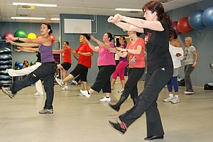 Zumba - An instructor coaches a Zumba class in a fitness center.