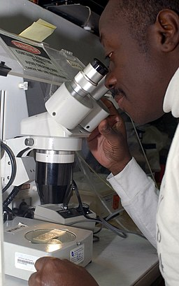 US Navy 021230-N-2864T-001 Damage Control 1st Class William Minniefield inspects microscopic samples of insulation taken from several different spaces on the ship