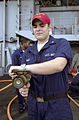 US Navy 030630-N-0413R-004 Damage Controlman 3rd Class Angel Diaz checks the nozzle of a fire hose on the fantail aboard USS Nimitz (CVN 68).jpg