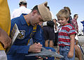 US Navy 030905-N-4459K-020 Lt. Cmdr. Dan Martin signs an F-14 Tomcat toy, for a child.jpg