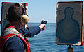 US Navy 040417-N-7781D-057 Ens. Michael Smith shoots a 9mm pistol during a pistol qualification shoot.jpg