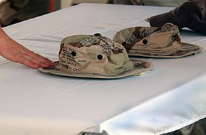 Nathan Bruckenthal - Boonie hats inscribed with messages of consolation are displayed during a memorial service to Bruckenthal, Christopher E. Watts, and Michael J. Pernaselli in April 2004.