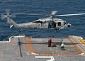 US Navy 040713-N-2651J-005 An MH-60S Knighthawk assigned to the Chargers of Helicopter Combat Support Squadron Six (HC-6) receives ammunition bound for a nearby Navy vessel from the flight deck aboard the amphibious assault shi.jpg