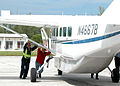 US Navy 040902-N-4779D-004 Personnel from Naval Air Station (NAS) Key West Operations Department push a Cessna Caravan airplane, owned by the Department of State, into a hangar.jpg