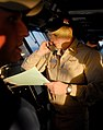 US Navy 061116-N-2959L-067 Lt. Cmdr. Paul Crawford makes a call to confirm the flight operations schedule while standing watch on the bridge of the Nimitz-class aircraft carrier USS Ronald Reagan (CVN 76).jpg