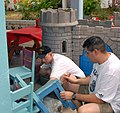 US Navy 070301-N-2191H-005 Lt. j.g. Brian Blackburn (left) and Hospital Corpsman 1st Class Jose Ramirez (right) assigned to USS Springfield (SSN 761) paints high chairs during a community relations (COMREL) project at the Hogar.jpg