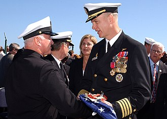USS John F. Kennedy (CV-67) - U.S. Navy Command Master Chief Charles L. Dassance presents the ensign to U.S. Navy CAPT Todd A. Zecchin, commanding officer of USS John F. Kennedy, during the ship's decommissioning ceremony in Mayport, Florida, on 23 March 2007.