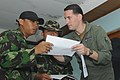US Navy 091011-N-9950J-088 Lt. Cmdr. Ian Johnston, air operations planner during the Indonesian humanitarian assistance operation, reviews a flight plan with Indonesian army officers at Tabing Airfield.jpg