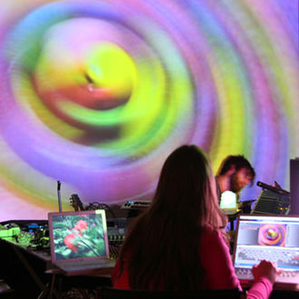 VJing - A VJ working with computers with their projection in the background.