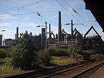 View from a train of numerous smoke stacks, tanks and pipes.