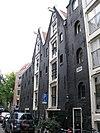 foto van Pakhuiscomplex op scherpe hoek koggestraat/teerketelsteeg bestaande uit: a) een dubbel pakhuis met voorgevel eindigend in twee gewijzigde punttoppen en aan de achterzijde twee puntgevels