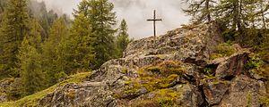 Wandeltocht rond Lago di Pian Palù (1800 m). in het Nationaal park Stelvio (Italië). Houten kruis boven op rots naast de bergweg 02.jpg