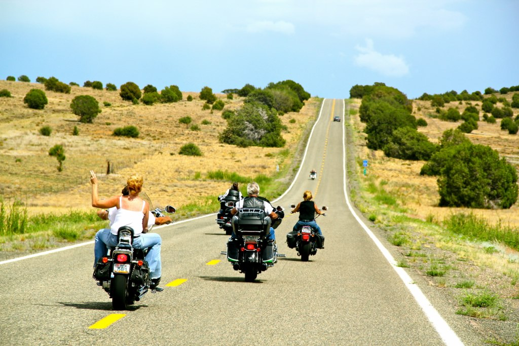 Waving from motorcycle on open road