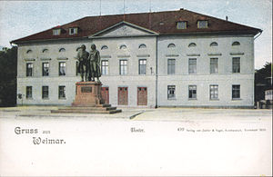 "Picture postcard of a large, three-storey building. There is a city square in front of the building. About 10 meters in front of the entrance to the building there is a large bronze statue of two men; the statue is on top of a stone pedestal. The postcard has a white band at its bottom with the printed phrases ""Grüss aus Weimar"", ""Theater"", and ""499 Verlag von Zedlar und Vogel, Kunstanstalt, Darmstadt 1899."""