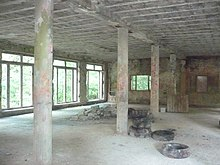 An empty room in an abandoned building with no finishes, cement structural systems visible, support columns in the middle, empty openings along a left brick wall through which a forest can be seen, and cement blocks and tires piled on the floor