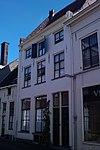 foto van Pand met verdieping en hoog zadeldak, evenwijdig aan de straat, tussen puntgevels met rollagen