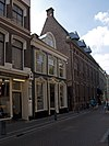 foto van Pand met lijstgevel met dakkapel, gepleisterde raam- en deuromlijstingen met versierde boogbeeindigingen en gepleisterde plint met panelen