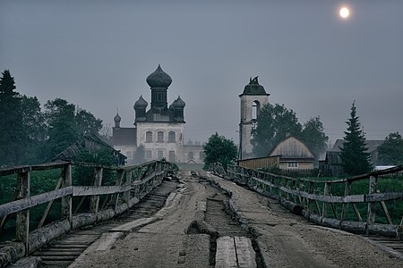 Old wooden bridge and church in Leshino