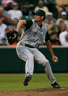 "A man in a green baseball cap and grey baseball uniform with ""TAMPA BAY 15"" on the chest prepares to pitch a baseball with his left hand."