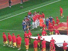 A team in blue shakes hands with a team in red. In the foreground are people wearing red shirts and gold shorts assisting with the presentation of the game.