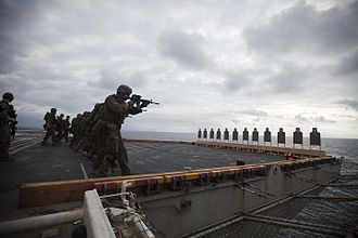 31st Marine Expeditionary Unit - Marines and sailors with the Maritime Raid Force, 31st Marine Expeditionary Unit, approach and engage paper targets during a live fire exercise on the flight deck of the USS Bonhomme Richard (LHD 6)